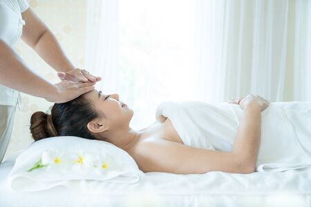 Thai facial massage. head face thai massage female with closed eyes. Beautiful young woman enjoying facial massage in spa salon