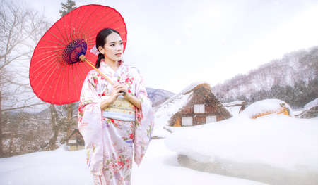 Asian woman tourists. Japanese girl holding a red umbrella. Beautiful Female wearing traditional japanese kimono In famous tourist spots in Shirakawa is a village located Gifu Prefecture, Japan. Stockfoto