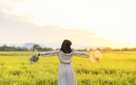 Asian women in fresh air grassland. Young asian woman enjoying freedom. A woman with flowers and a hat.