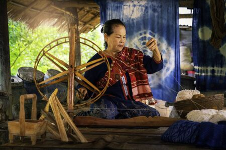 Craftsmen of Thai indigo cotton. Local Master are the original Indigo Cotton Weaving in the community of Sakon Nakhon province. Thai old woman shows weaving spinning natural colorful threads or yarn.
