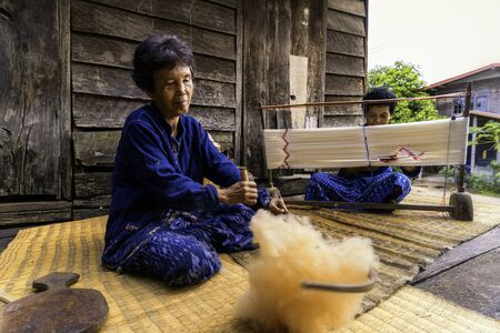 Forging the cotton and making mudmee cotton. White cotton wool and spinning yarn from cotton. Process of weaving, dyeing, weaving ancient Thailand as cotton natural indigo. Banque d'images