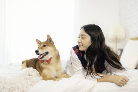 Pet Lover Concept. Woman and Shiba inu dog Looking forward. Asian girl and puppy looking forward in bed room.