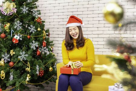X-mas and holiday concept. Happy girl with gift box. woman in Christmas cap hands present wrapped with gold paper and red ribbon.