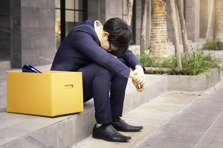 Unemployed man, The economic downturn made people unemployed, Desperate businessman sitting hopelessly on stair in central business district due to unemployment. failure, desperation, depression.