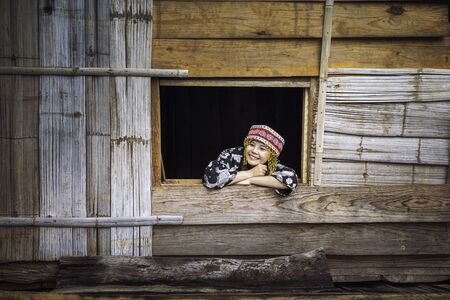 Tourists wearing hill tribe clothes. An Akha on the window. Tourists wearing Hmong hill tribe clothes and sitting with mobile, by window.