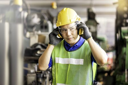 Professional technicians wear protective equipment and hard hats in large industrial plants. Protective and Safety Equipment eye wear, ear plug, vis clothes and protective helmet. Reklamní fotografie
