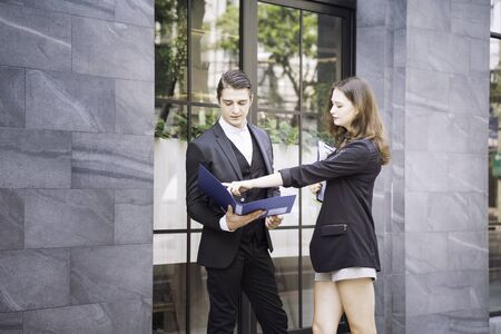 Business discussions between Caucasian people. Business people are talking and smiling while standing on stair of the office building.