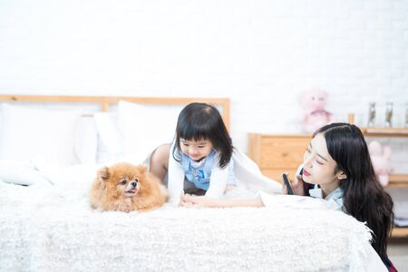Pet Lover concept. Old sister and sister woman selfie Pomeranian Spitz dogs with mobile phone. Asian girl and young woman and puppy looking forward sitting on the bed in bed room.