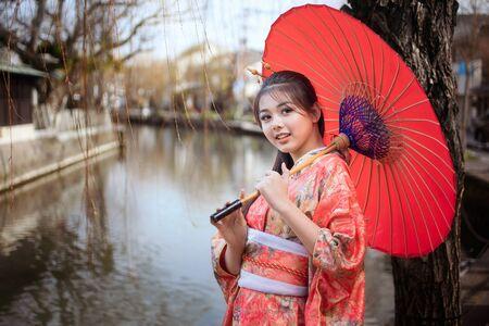 Asian woman tourists. Japanese girl wearing a kimono holding a red umbrella. Beautiful Female wearing traditional japanese kimono In famous tourist spots in Yanagawa river Fukuoka, Japan.