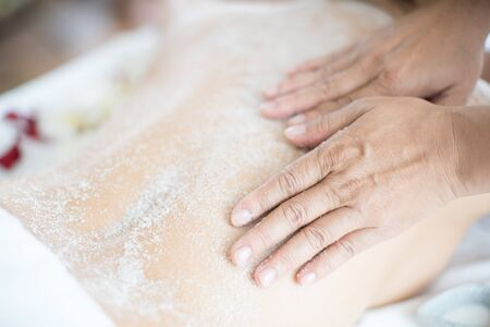 Asian woman massaging spa with salt.