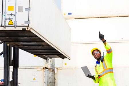Looking forword. Foreman using laptop computer in the port of loading goods. Foreman showing thumbs up on Forklifts in the Industrial Container Cargo freight ship.