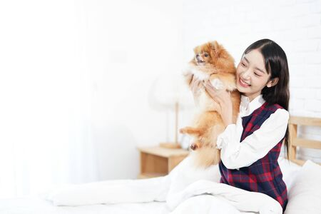 Pet Lover Concept. Girl and small dogs Pomeranian Spitz Looking forward. Asian girl and puppy looking forward in bed room. Space for text. Archivio Fotografico