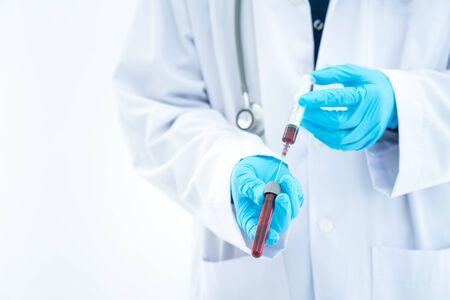 Doctor Hand holding test tube. Asian doctor holding virus and bacteria in bloods sample tube. Hand of a lab technician holding blood tube test. BD Vacutainer blood tube. Stock fotó