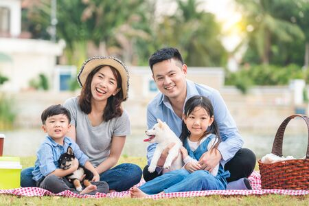 An Asian family plays with a Shiba Inu dog. Family has father, mother and son, daughter. Picnicking in the garden. Stock Photo