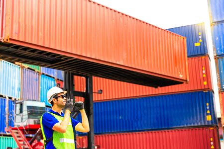 Foreman is controlling air or sea freight. Foreman works with radio to communicate with forklift drivers. Stock Photo