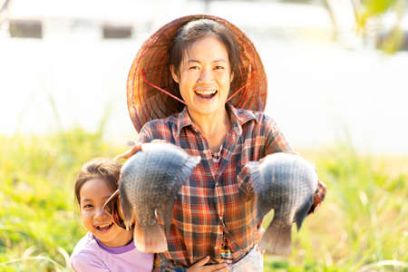 Mother and daughter show off a big tilapia raised in floating baskets on the Mekong River.