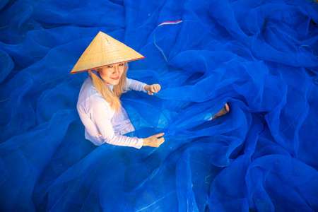 Vietnamese girls are cleaning fish trap mesh.