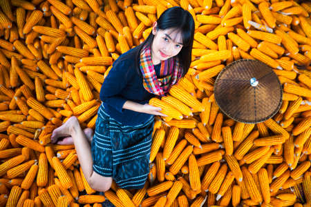 Thai girl Wearing a national hat and dress, choose corn.