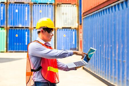 Foreman or Operator Ordering of moving containers with laptop computer. Foreman looking forward on Forklifts in the Industrial Container Cargo freight ship.