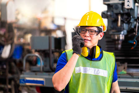 Portrait of an engineer at work in the industry. Foreman works with radio to communicate. Professional technicians work through the radio. In factories that have machinery