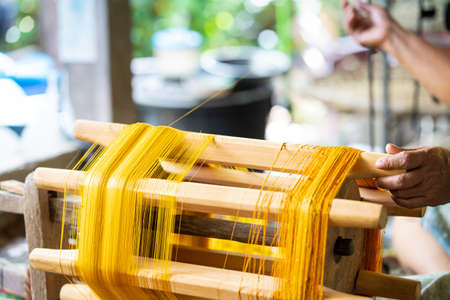 Silk raising for silk threads. yarn warping machine in a textile weaving crafsmanship. Hand of woman weaving and spinning natural colorful threads or yarn. Stock Photo