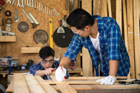 Two carpenters are working in a wood factory. The carpenter is sketching the wood.