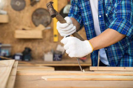 The carpenter is using a hammer to chisel To trim wood