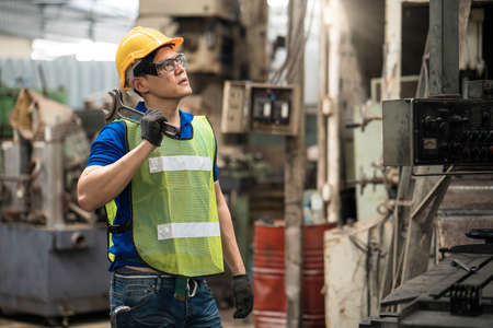 Professional engineer in the factory Engineers are proud of their work, carrying a wrench. Technicians are working in factories that use industrial machinery.
