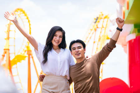 Young men and women playing at the amusement park. A couple in theme park. Stockfoto