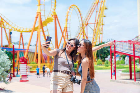 Teenage girls traveling in an amusement park. A group of female friends are taking pictures of themselves in an amusement park.