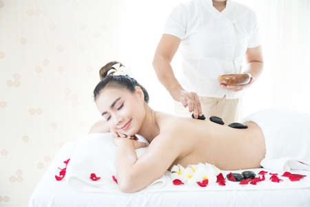 The young woman is spa massage in the spa room. Spa with hot stones.