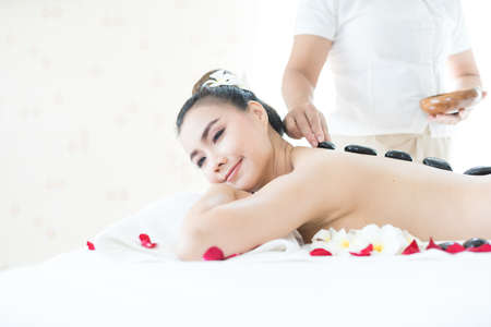 The young woman is spa massage in the spa room. Spa with hot stones. Thai spa.