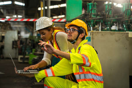 Professional engineers and technicians are inspecting machine operations via a laptop computer. Stockfoto