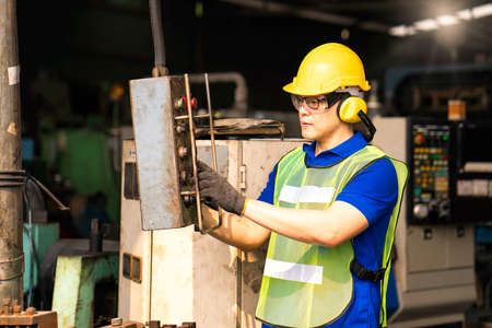 Professional technicians are operating the machine with a remote control in an industrial factory.