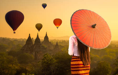 A young Burmese woman is walking with a red umbrella. Young girl and Sunrise many hot air balloon with stupas in Bagan, Myanmar. space for text.