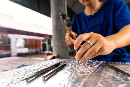Hand of a woman cutting silverware. Thai craftman are making silverware. A craftsman carves intricate drawings into silver or aluminium which is used for silverware. Stockfoto