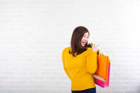 An Asian woman holding a shopping bag standing on a white brick background