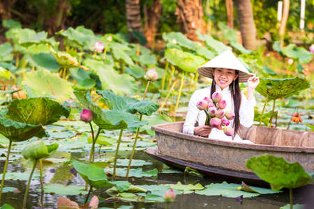 Vietnamese Asian woman holding lotus flower sitting in a wooden boat.