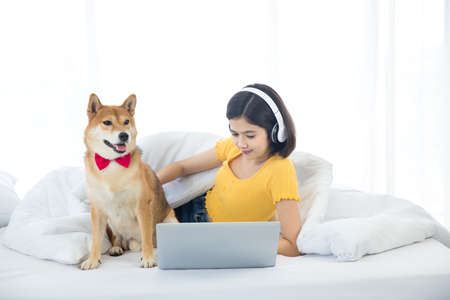 A girl is using a laptop computer with a Shiba Inu in her bedroom.