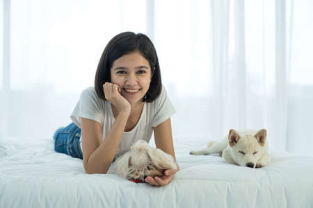 A girl lying in a bed where a white Shiba and maltese are sleeping in the bed.