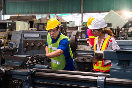 Technicians and engineers are working on industrial machines in the factory.