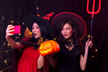 Two women taking photos with mobile phone at Halloween party. Selfie with mobile phone in the party.