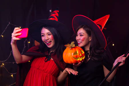 Two women taking photos with mobile phone at Halloween party. Selfie with mobile phone in the party. A woman dressed as a witch and a devil holding a pumpkin.