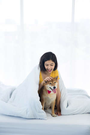 A girl imitating a Shiba Inu dog. Girl with her dog in the bedroom