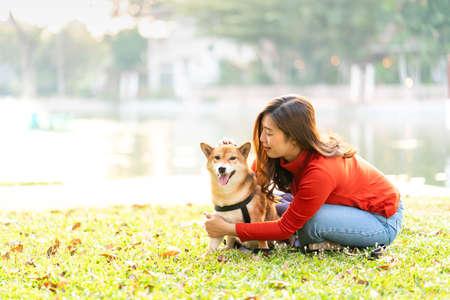 Asian woman hugging Shiba Inu in a park