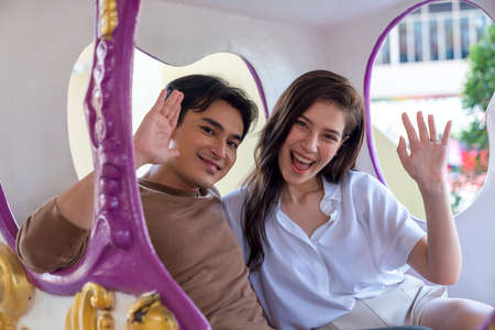 Couples play rides in the amusement park. Asian couple waving to the camera.
