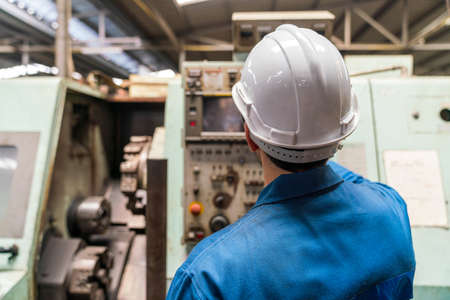 Technicians work at industrial machines in large factories. Stockfoto