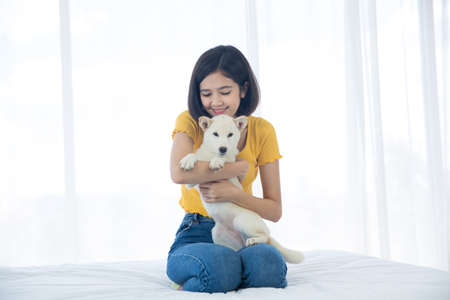 A girl hugging a Hokkaido Inu or Shiba Inu dog on a bed in a white bedroom. Stockfoto