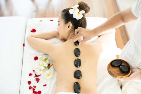 A spa masseuse is placing a hot stone on an Asian woman. Lying in a relaxing massage spa. Stockfoto