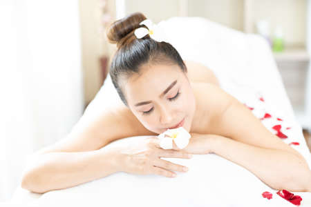 Asian woman relaxing with floral scent in spa massage parlor. Stockfoto